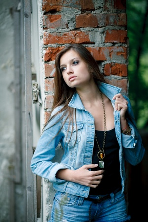 sexy young female outdoors wearing a jean jacket looking aside w brick wall background photo