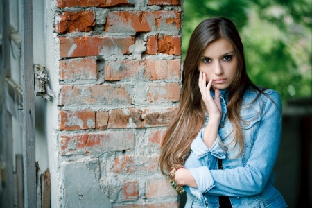 young female leaning against the wall outdoors wearing a jean jacket looking at camera photo