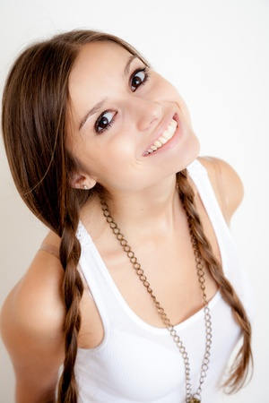 affable: smiling girl with braids looking at camera on white background Stock Photo