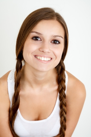 smiling girl with braids looking at camera on white background Stock Photo