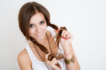 young female playing with her braids and smiling on white background Stock Photo