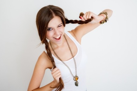 young female playing with her braids and winking on white background photo