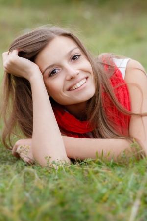 unconcerned: mujer joven tumbado en la hierba sonriendo feliz