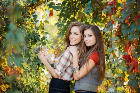 two girlfriends outdoors smiling looking at camera with wild grapes in background photo