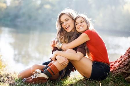 amistad: dos mujeres jóvenes sentados en el césped con buen tiempo