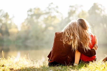 two young women sitting on grass hugging rear view Stock Photo