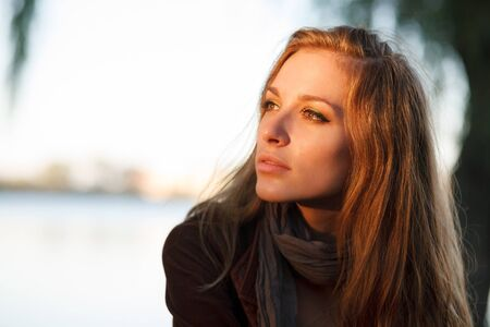 jonge vrouw die bij zonsondergang close-up Stockfoto