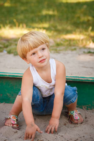 little girl sits in sandbox playing looking away Stock Photo