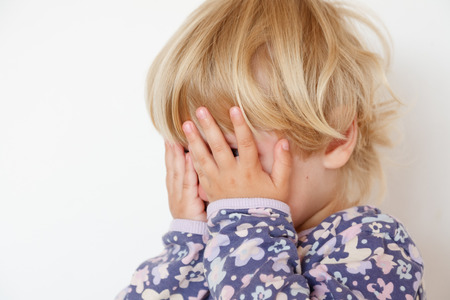 little girl hiding face with hands closeup on white photo
