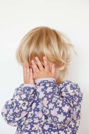 little girl hiding face with hands on white photo