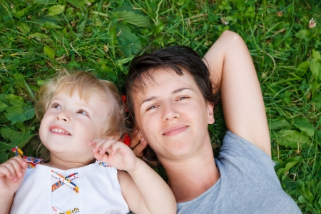 mother and daughter lying down on grass having good time closeup photo