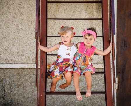 two little girls sitting on stairs barefoot outside Stockfoto