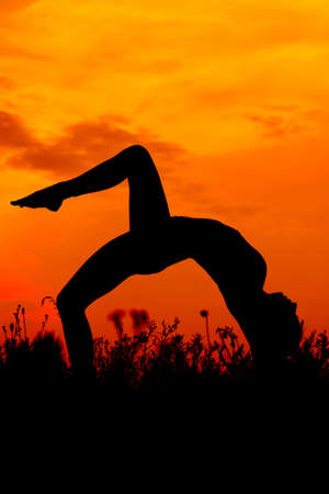 silhouette of female doing yoga exercises on sunset sky photo