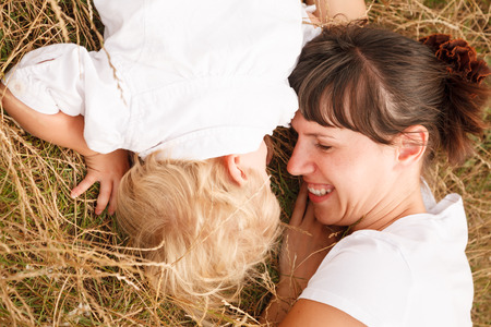 mother and her little daughter lying down on grass happy smiling view from above photo
