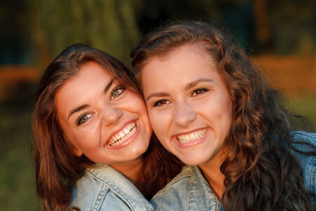 jeanswear: close-up portrait of two happy teenage girls outdoors in jeans wear smiling looking away