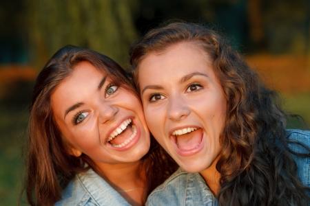 jeanswear: close-up portrait of two happy teenage girls outdoors in jeans wear shouting looking away