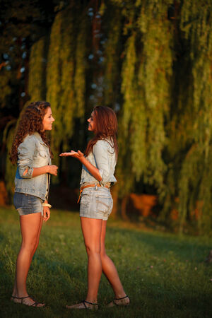 jeanswear: two teenage girls outdoors in jeans wear talking looking at each other