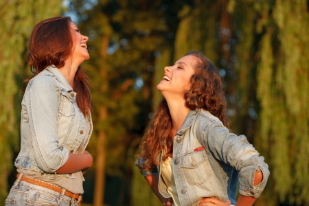 jeanswear: two teenage girls outdoors in jeans wear laughing looking at each other Stock Photo