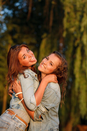 jeanswear: two teenage girls outdoors in jeans wear hugging looking at camera Stock Photo