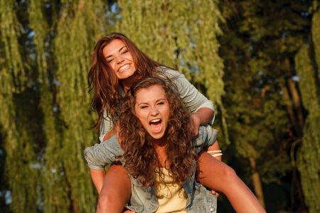 jeanswear: teenage girl giving her girlfriend piggyback ride in park