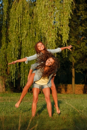 jeanswear: teenage girl giving her girlfriend piggyback ride in park