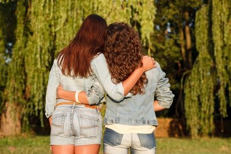 jeanswear: two females outdoors in jeans wear rear view