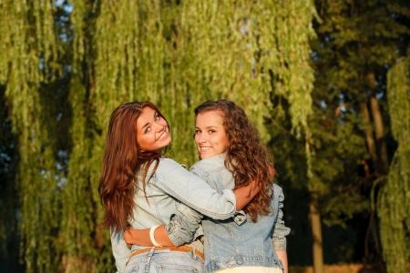 jeanswear: two teenage girls in jeans wear outdoors hugging rear view