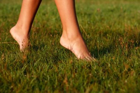 裸足の緑の草の上を歩いて女性の足のクローズ アップ 写真素材