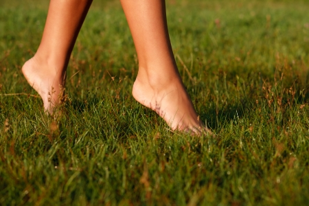 close-up of female legs walking on green grass barefoot photo