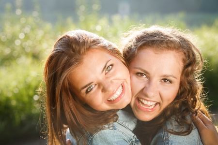 jeanswear: close-up of two happy teenage girls outdoors in jeans wear smiling hugging looking at camera