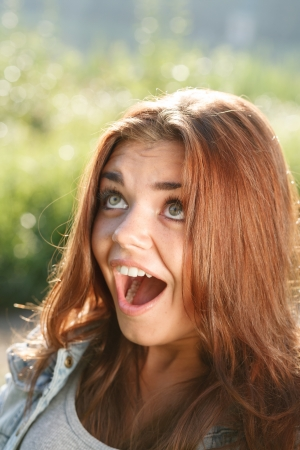 mouth opened: close-up portrait of surprised teenage girl outdoors with mouth opened looking away