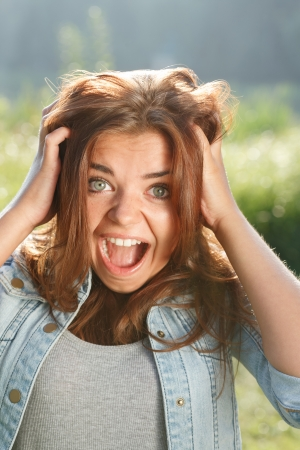 mouth opened: close-up portrait of shocked teenage girl outdoors with mouth opened looking at camera