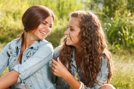 jeanswear: two girlfriends in jeans wear outdoors sitting  having fun looking at each other