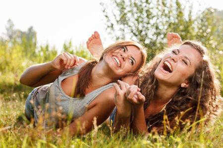 riendo: dos amigas en las camisetas que se acuesta en la hierba riendo con una buena vez Foto de archivo