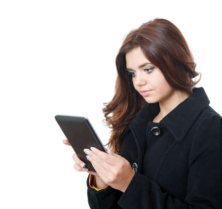 young female wearing a black coat using tablet pc isolated on white photo