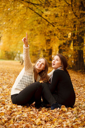 2 november: two young females sitting  in autumn forest