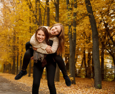 young female giving her friend piggyback ride in autumn forest photo