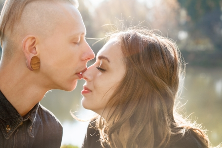 nose plugs: young male kissing females nose with eyes closed Stock Photo