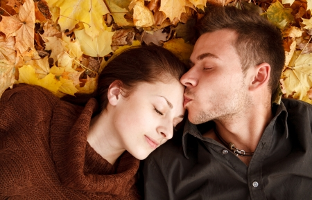 jong paar dat op de herfstbladeren ogen dicht hij kuste haar Stockfoto