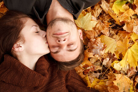 young couple lying down on autumn leaves eyes closed she kissing him photo