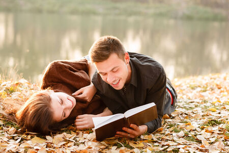 young man lying down near lake reading to his girlfriend book Stockfoto
