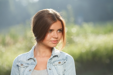 jeanswear: close-up portrait of beautiful teenage girl outdoors in jeans wear looking away