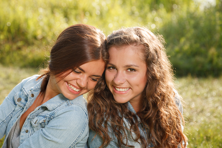 jeanswear: two girlfriends in jeans wear outdoors sitting back-to-back smiling