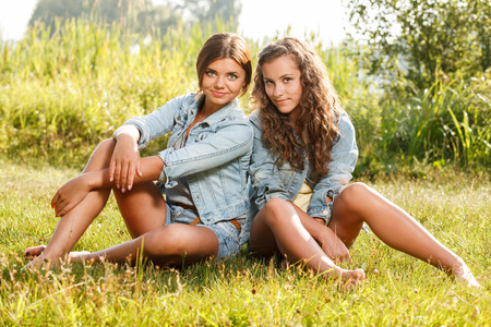 jeanswear: two girlfriends in jeans wear sitting on grass looking at camera Stock Photo