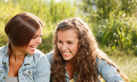 jeanswear: two girlfriends in jeans wear outdoors sitting  laughing Stock Photo