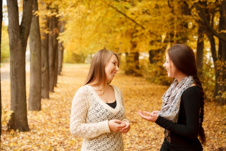 2 november: two young females talking in autumn forest smiling
