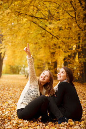 two young females sitting  in autumn forest photo