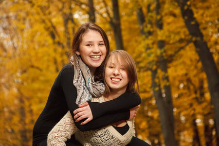 2 november: young female giving her friend piggyback ride in autumn forest