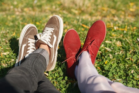 two pair of male and female legs in shoes lying on green grass photo