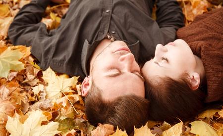 pareja durmiendo: pareja joven que se acuesta en las hojas de oto�o ojos cerrados